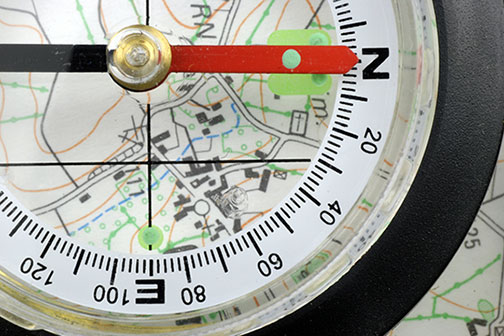 Close up of a magnetic compass lying on a topographical map
